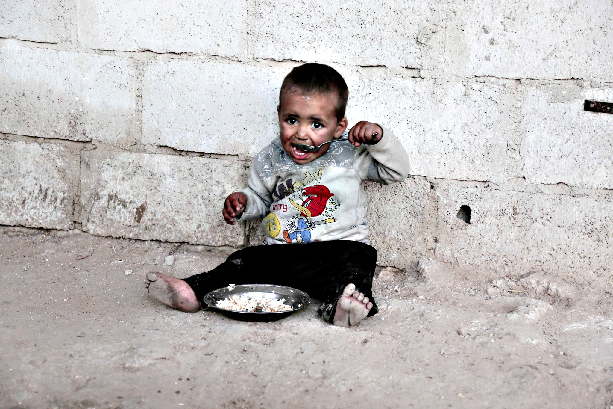 A child from the Abu Sleiman family has a lunch at his house in the Syrian town of Beit Nayem, in the rebel-held Eastern Ghouta region on the outskirts of the capital Damascus, January 14, 2016 (Photo: AFP/Amer Almohibany)