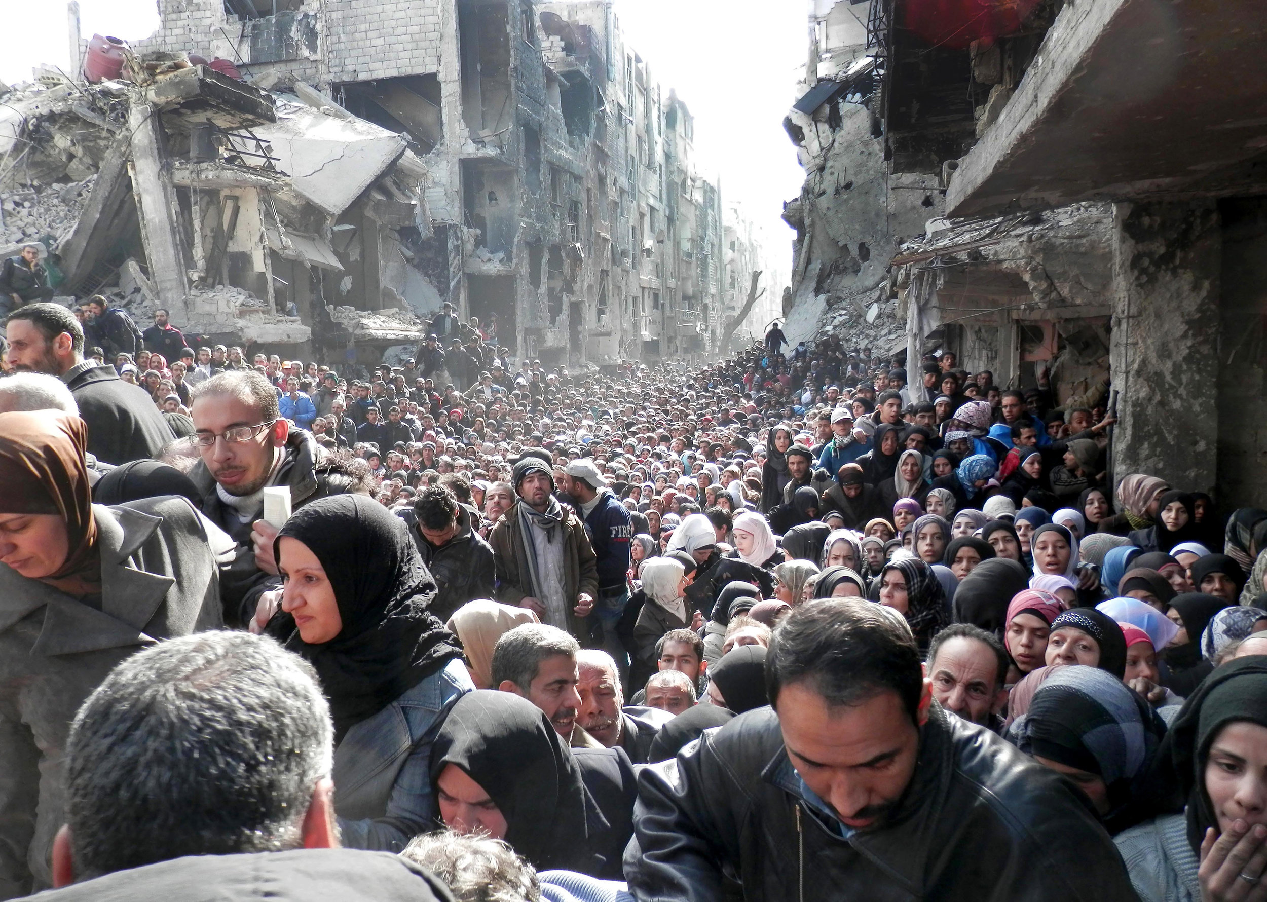 Palestinians at the besieged Yarmouk refugee camp in Damascus queue to receive food from the United Nations Relief and Works Agency for Palestine. Photo: AP