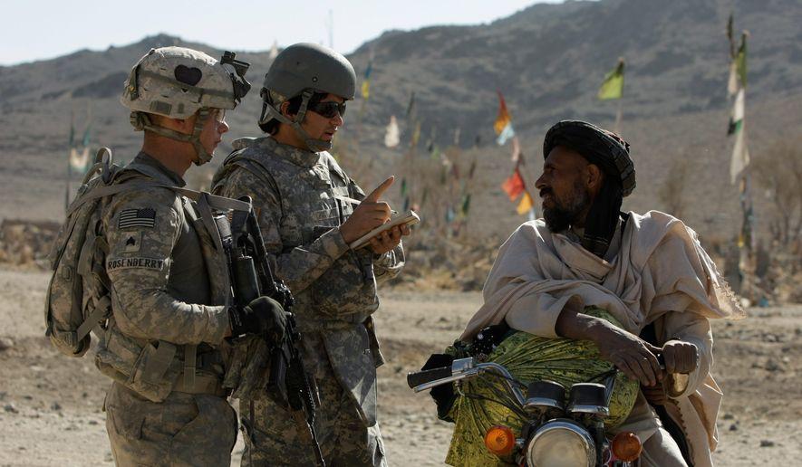 U.S. Army Sgt. Skyler Rosenberry of Pennsylvania (left) and an interpreter speak to an Afghan man in a village in Afghanistan. (AP)