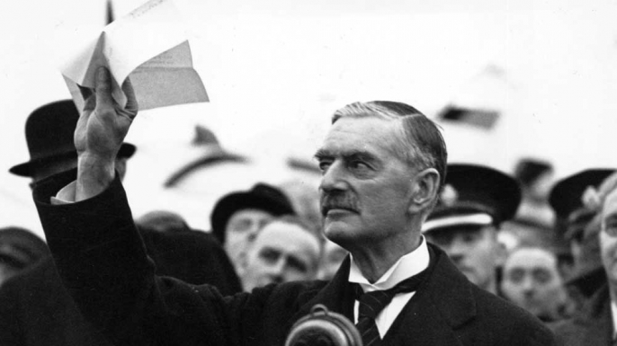 "Prime Minister Neville Chamberlain upon his return to London on September 30, 1938. This representation of appeasement and ""peace in our time"" has become iconic...but does the analogy hold? (History.com)"