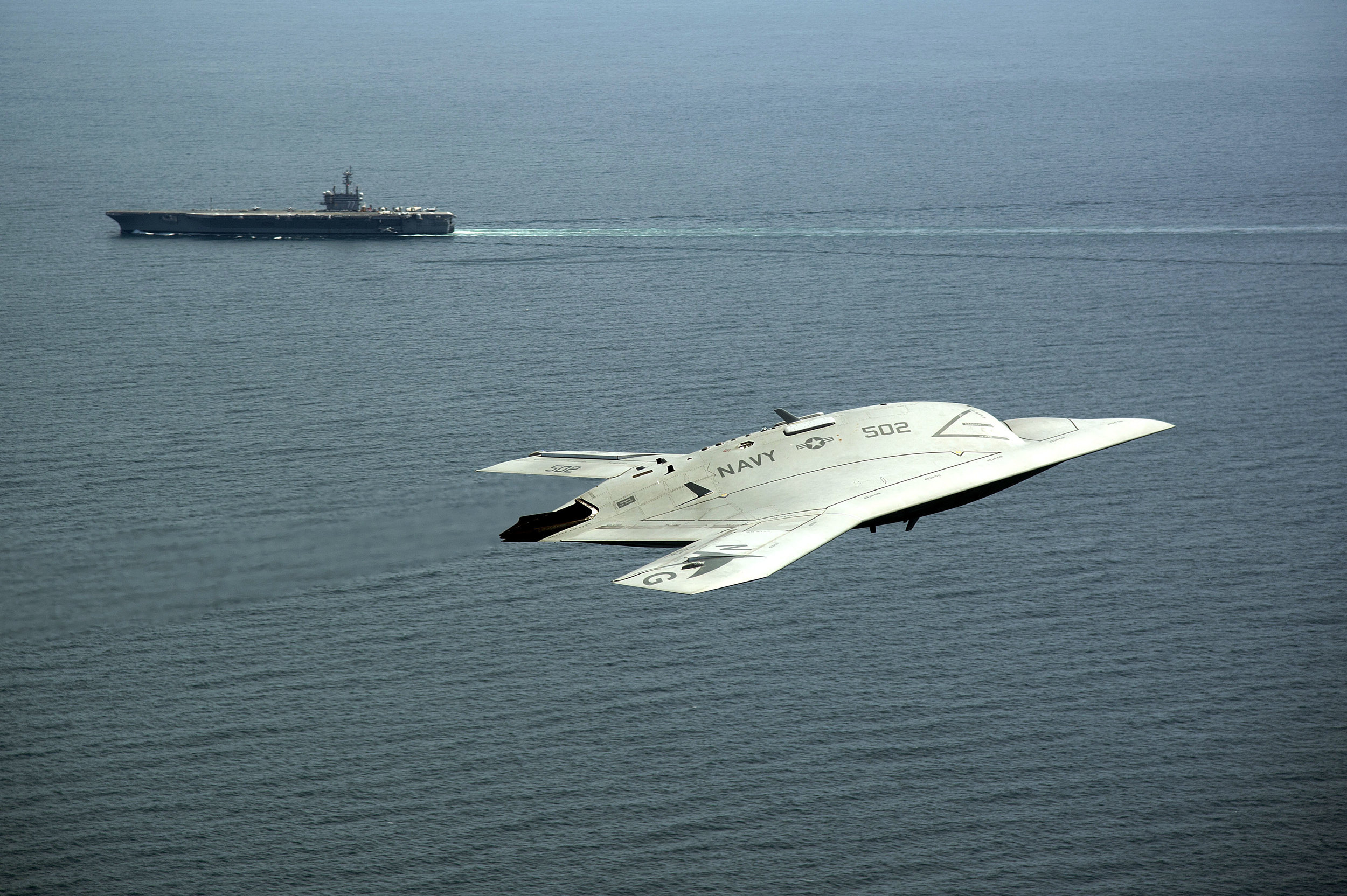 An X-47B Unmanned Combat Air System demonstrator flies near the aircraft carrier USS George H.W. Bush. | U.S. Navy photo by Erik Hildebrandt