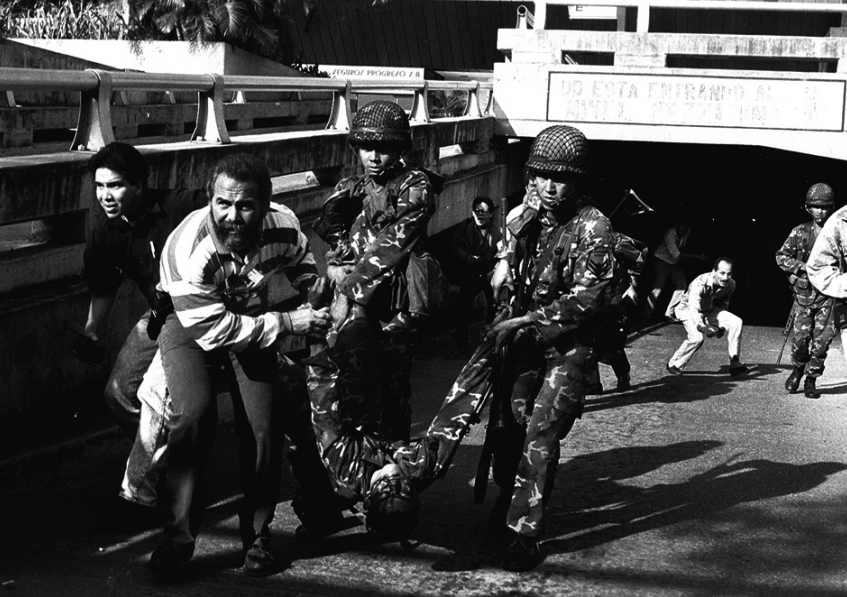 Rebelling military and civilian figures carry one of their wounded during the 1992 coup attempt by Hugo Chávez and his supporters.(Venezuelan National Library)