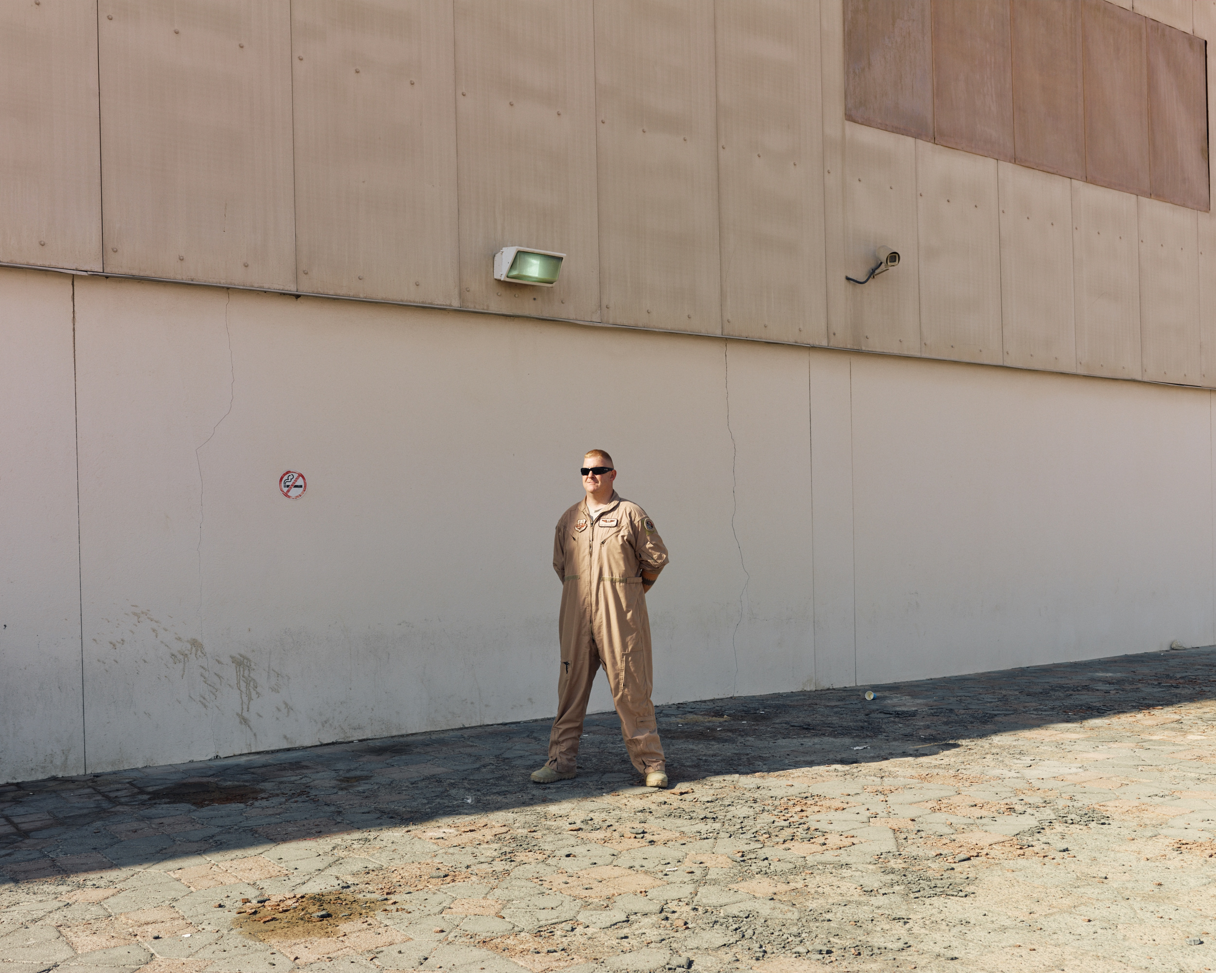 An airman stands outside a hangar at the Air Warfare Center in Al Dhafra, UAE. ( Jason Koxvold )