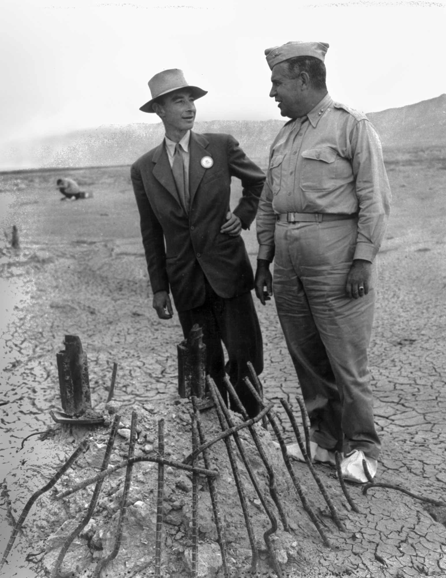 General Leslie Groves and Dr. Robert Oppenheimer at the site of the Trinity test in September 1945. The white overshoes were to prevent fallout from sticking to the soles of their shoes. (U.S. Army Corps of Engineers/Wikimedia)