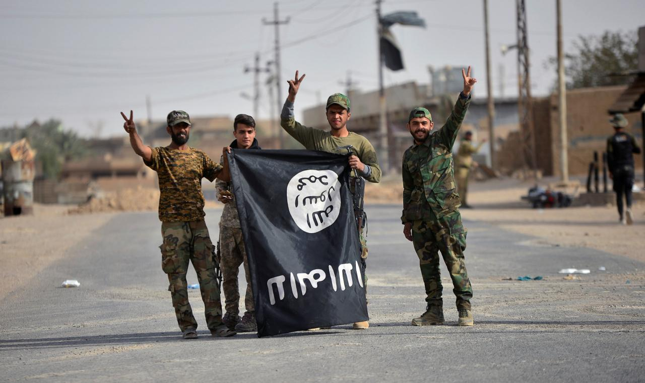 Shi'ite Popular Mobilzation Forces (PMF) fighters carry the Islamic State militants flag downward after liberating the city of Al-Qaim, Iraq November 3, 2017. (Reuters)