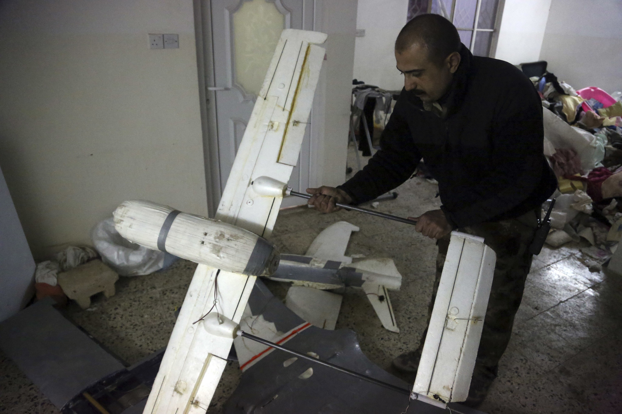 An Iraqi officer inspects drones belonging to Islamic State militants in Mosul, Iraq on Jan. 27, 2017. The Islamic State is hacking store-bought drone technology, using rigorous testing and tactics that mimic those used by U.S. unmanned aircraft to adapt to diminishing numbers of fighters and a battlefield that is increasingly difficult to navigate on the ground. (Khalid Mohammed/AP)