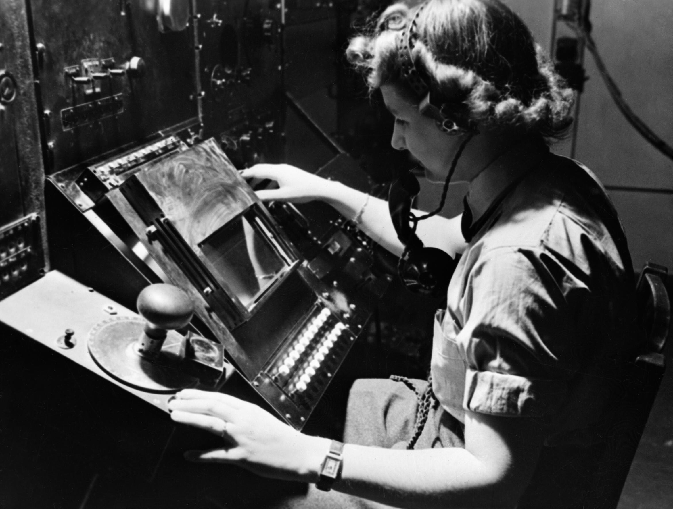 Chain Home: WAAF radar operator Denise Miley plotting aircraft on the cathode ray tube of an RF7 Receiver in the Receiver Room at Bawdsey CH. (Wikimedia Commons)