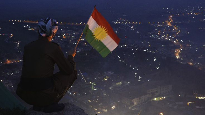 A man is photographed holding the Kurdish national flag over Akre city in the Kurdistan Region during the Kurdish New Year celebration of Newroz , March 20, 2015. (Claudio von Planta)