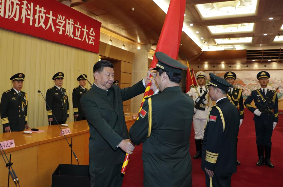 Chinese President Xi Jinping, also the chairman of the Central Military Commission, presents the heads of the People's Liberation Army Academy of Military Science with the military flag in 2017. (Li Gang/Xinhua)