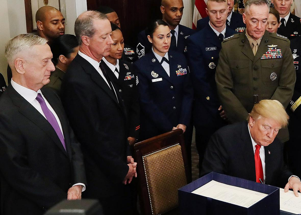 Flanked by members of the military, U.S. President Donald Trump signs the National Defense Authorization Act for Fiscal Year 2018. (Mark Wilson/Getty Images)