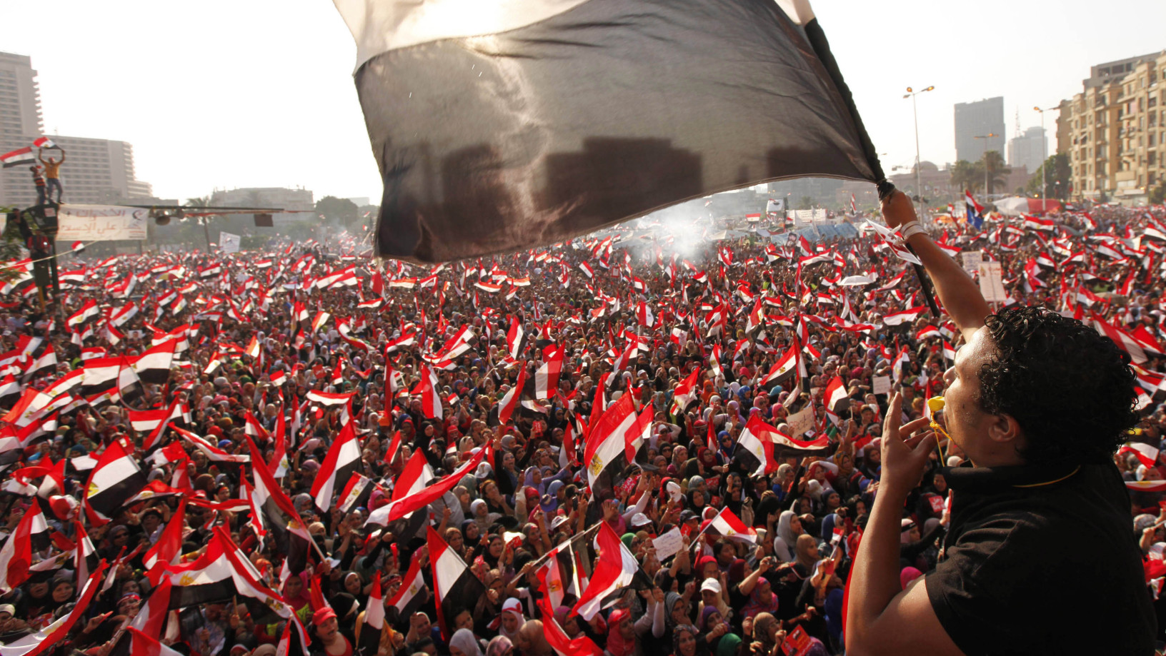 Protesters opposing Egyptian President Mohammed Morsi wave flags in Tahrir Square in Cairo in 2013. Shortly afterward, the military staged a coup, ousting Morsi and suspending the constitution. (Mohamed Abd El Ghany/Reuters)