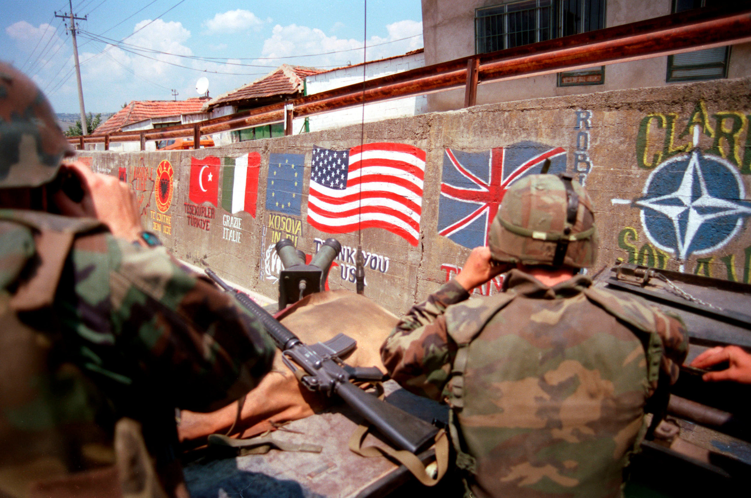 U.S. Marines from the 2nd Light Armored Reconnaissance Battalion pass flags of the NATO nations and messages of thanks painted on the retaining wall of a road in a village in Kosovo on July 5, 1999. (SGT Craig/DOD Photo)