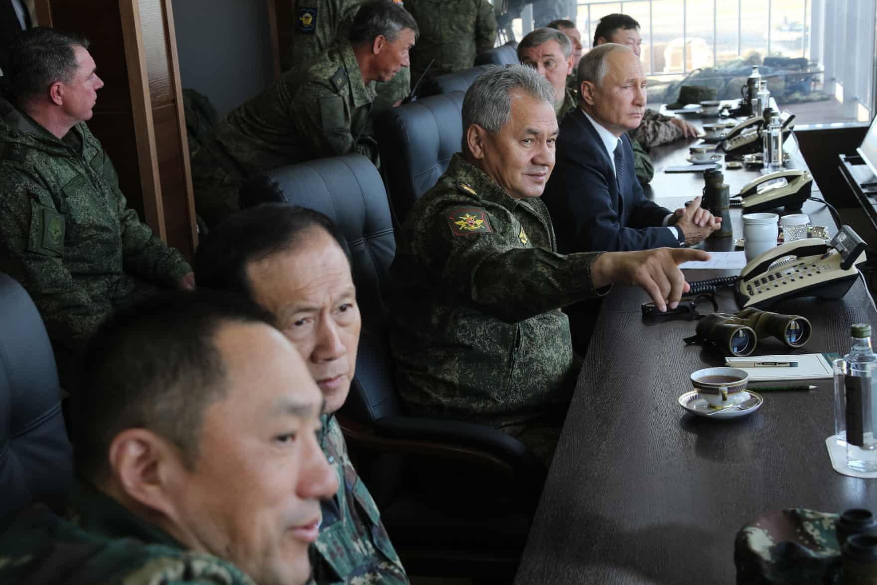 Russia's defence minister, Sergei Shoigu, and the president, Vladimir Putin, watch the Vostok war games with military personnel (Vadim Savitsky/Tass)