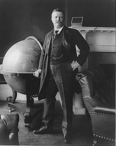 Theodore Roosevelt standing beside large globe in the White House, 1903 (Wikimedia)