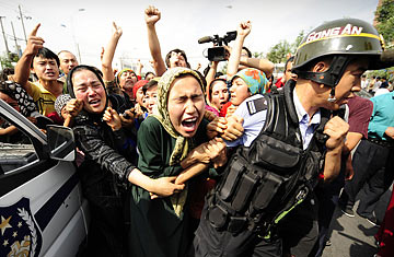 Ethnic Uighur women grab a riot police officer as they protest in Urumqi, in China's far west Xinjiang province, on July 7, 2009. (Peter Parks/AFP/Getty)