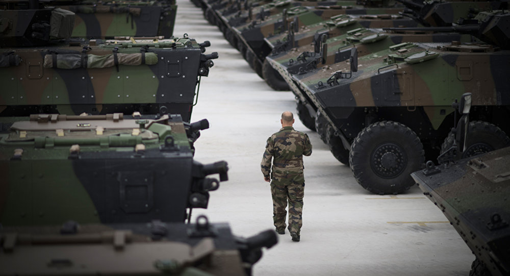 A soldier walks among French armored vehicles at Mourmelon Military Camp in northeastern France (AFP)