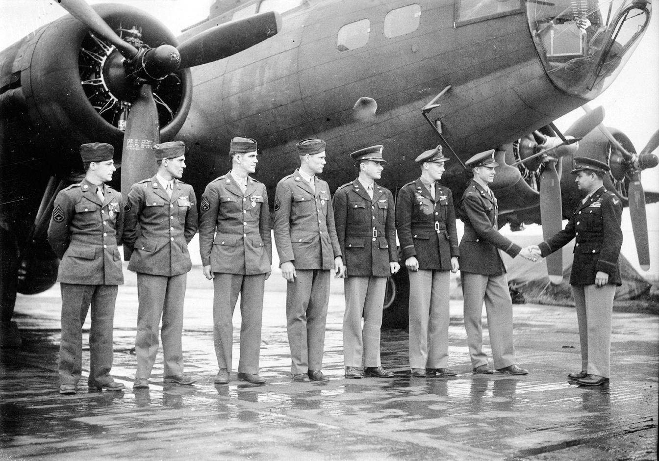 Colonel Curtis LeMay officially congratulates a bomber crew of the 306th Bomb Group in front of their B-17 Flying Fortress at Chelveston Airfield, England, 2 June 1943. (USAAF Photo/Wikimedia)