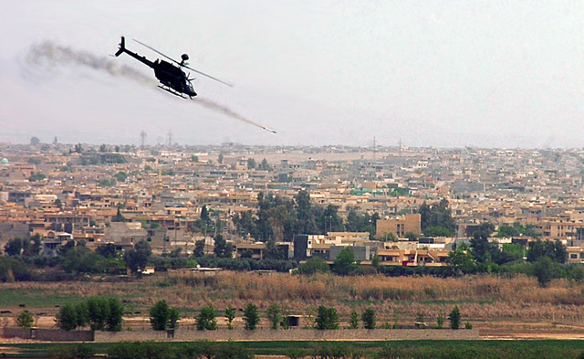 An OH-58 Kiowa helicopter fires a 17 pound rocket over the city of Mosul, Iraq. (BlackFive)