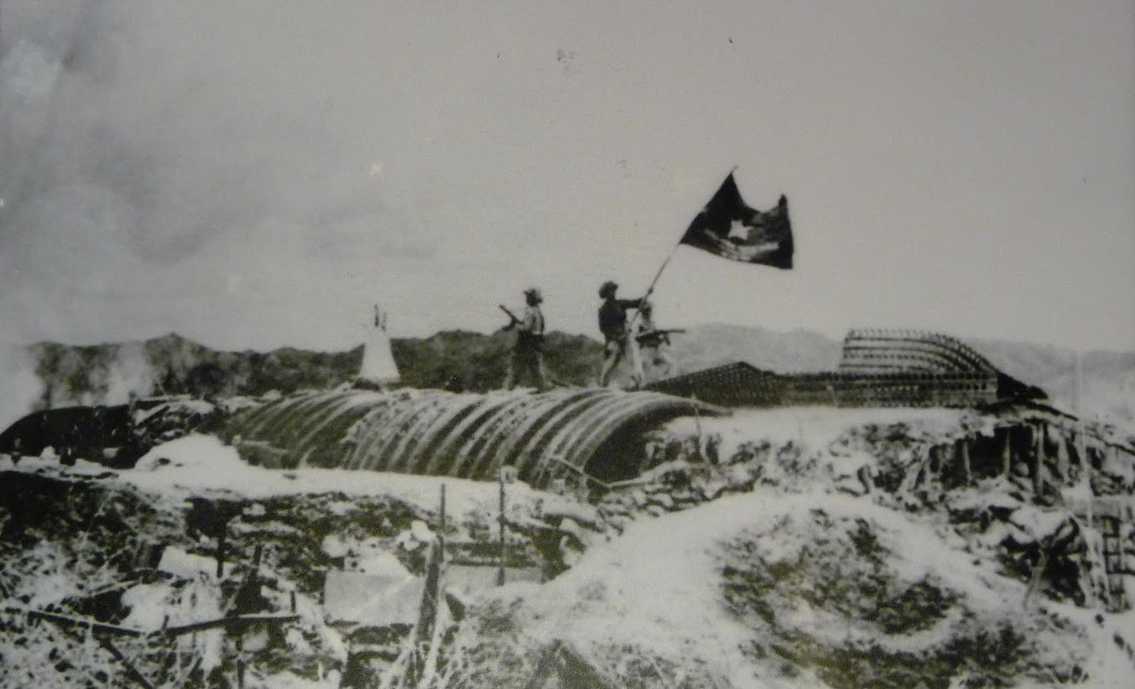 Viet Minh troops plant their flag over the captured French headquarters at Dien Bien Phu (Wikimedia)