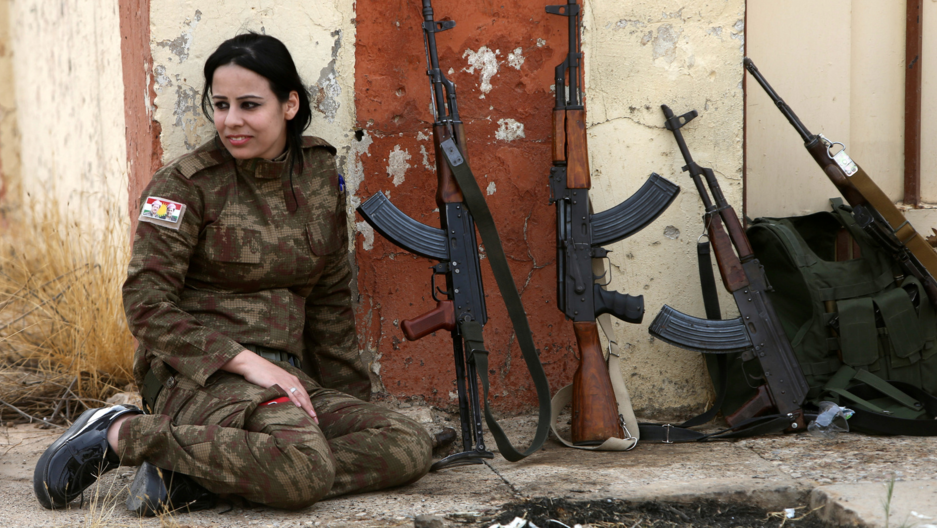 A Yazidi woman who joined the Kurdish Peshmerga forces sits next to rifles in the town of Bashiqa, after it was recaptured from the Islamic State. (Alaa al-Marjani/Reuters)