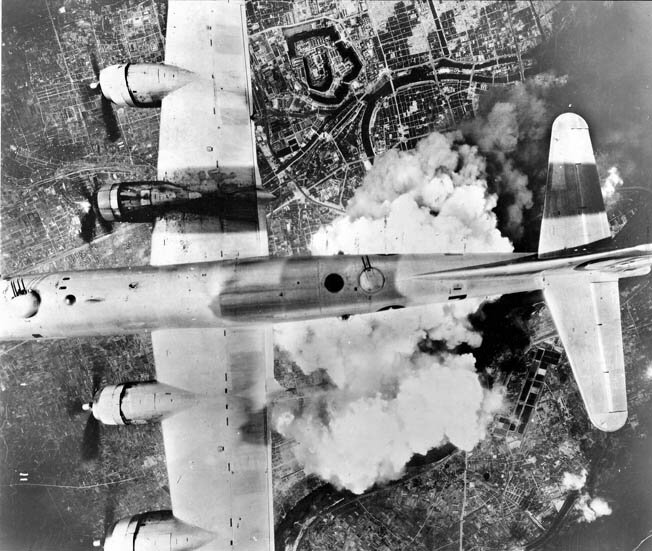 With smoke and dust rising below, a B-29 bomber flies over Osaka in June 1945 (Warfare History Network)