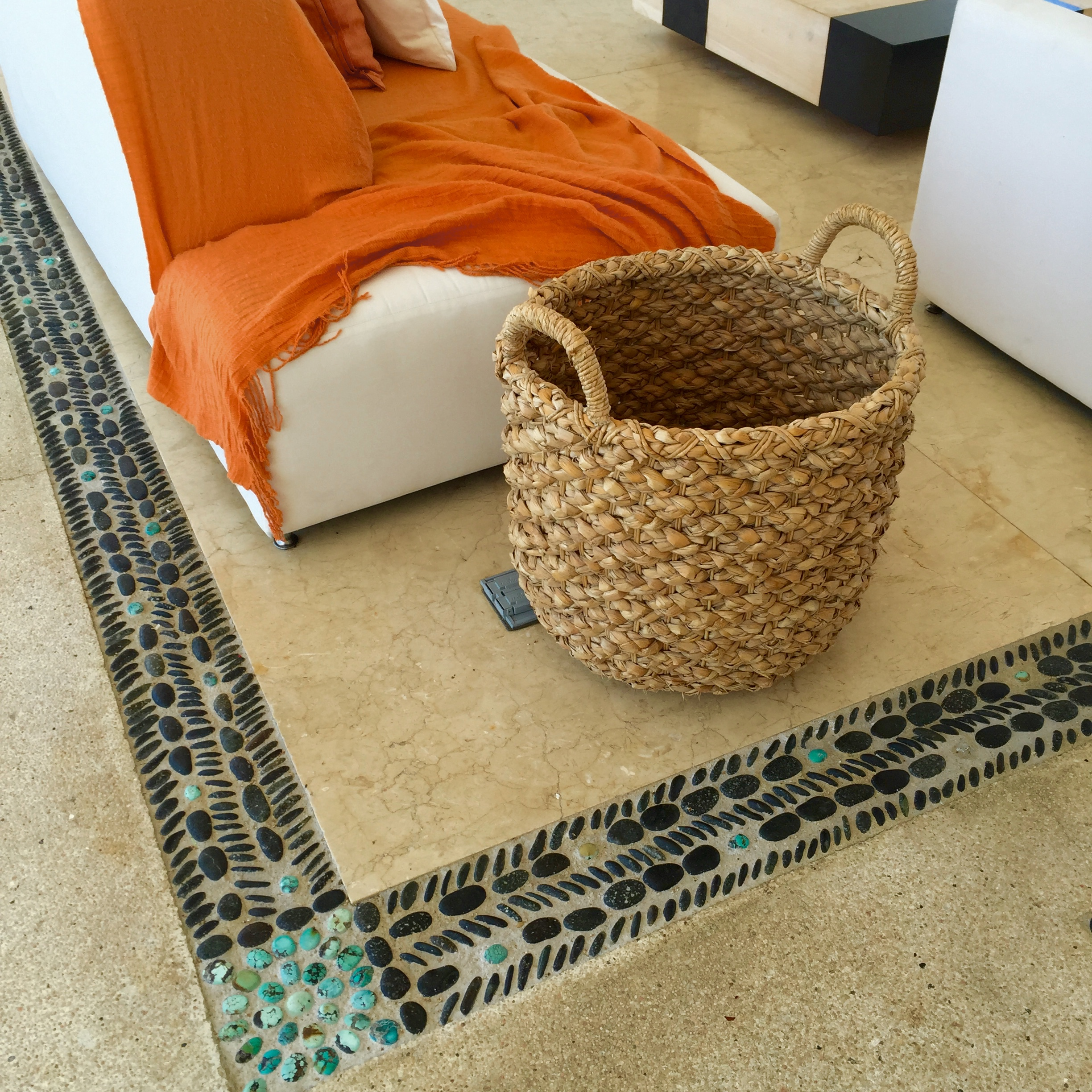 Natural woven baskets and orange and white in the main lobby.