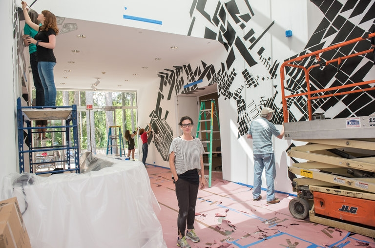 The artist Caitlin Masley at the Katonah Museum of Art in Katonah, N.Y. Behind Ms. Masley, volunteers filled in her tracings inspired by images of Modernist architecture.     Credit:Margaret Fox