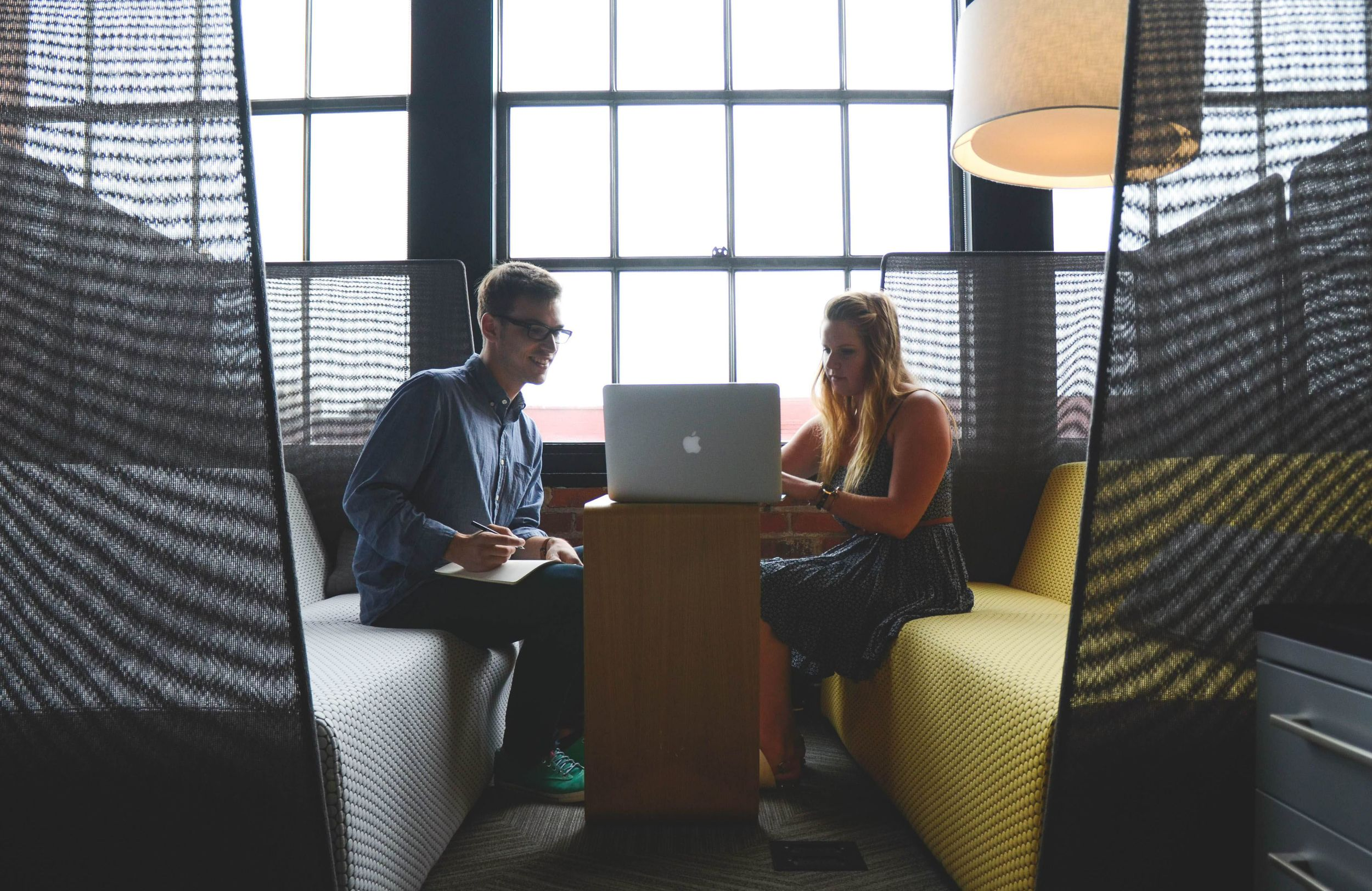 Man and woman looking at a Macbook in a cool office