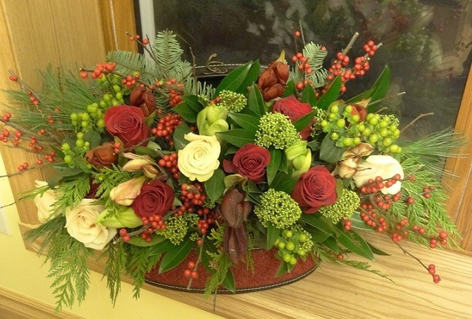 Assorted amarylis, red ilex berries, green berry scimmia, freedom and sahara roses in valise.jpg