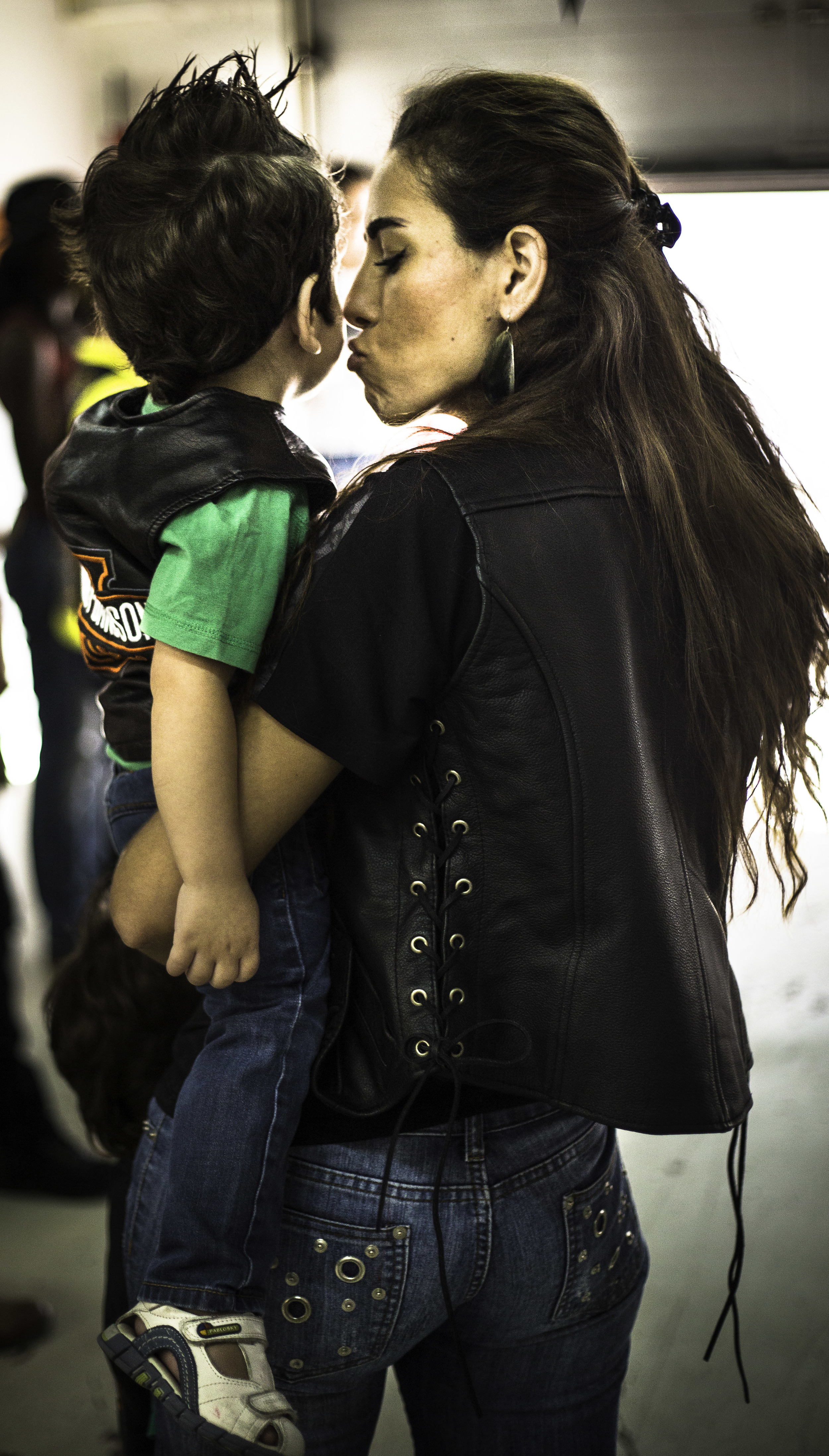 A woman kisses her son at the Harley-Davidson women-only Garage Party.jpg