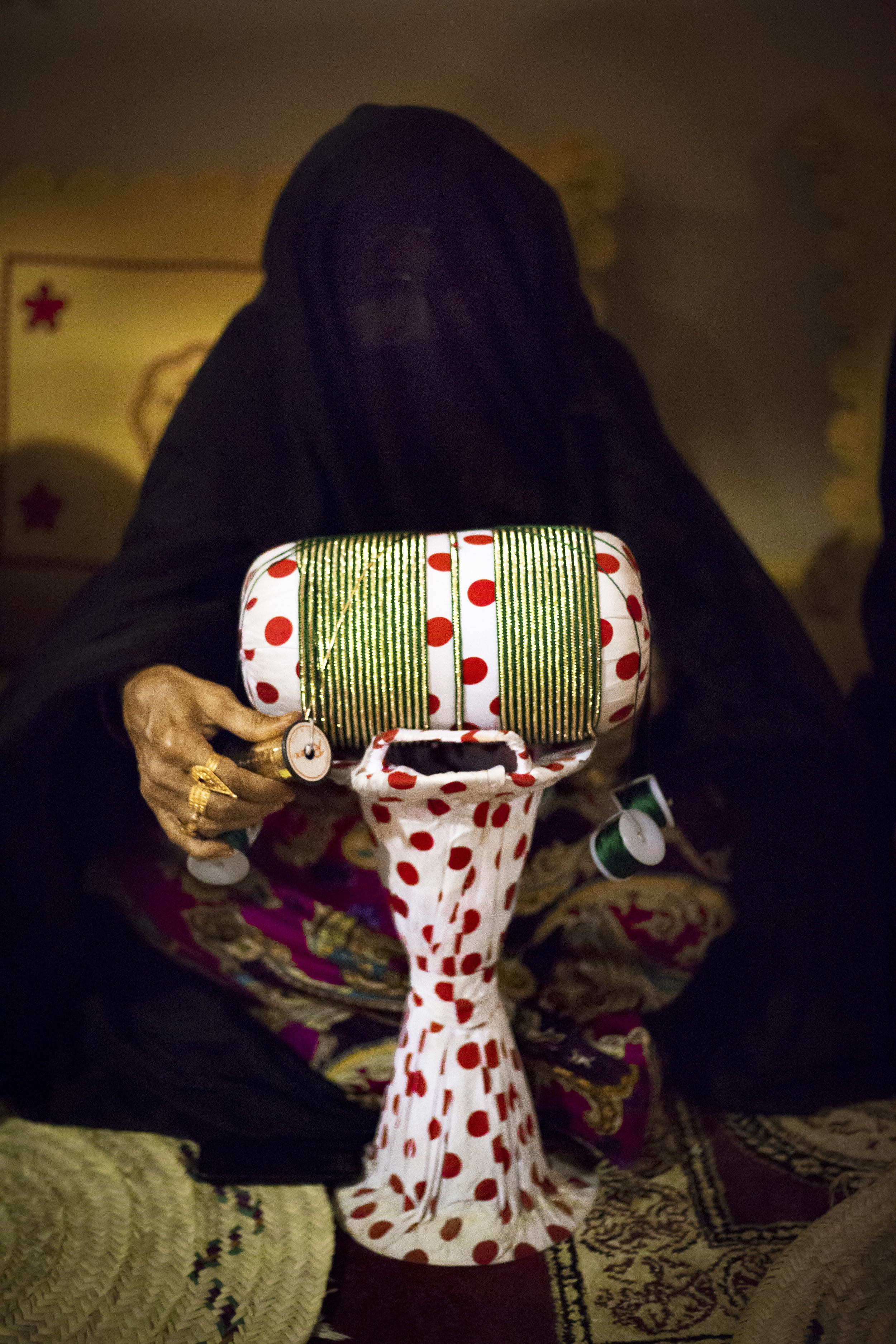 An Emirati woman demonstrates a traditional method for making ornate trimmings for abayas.jpg