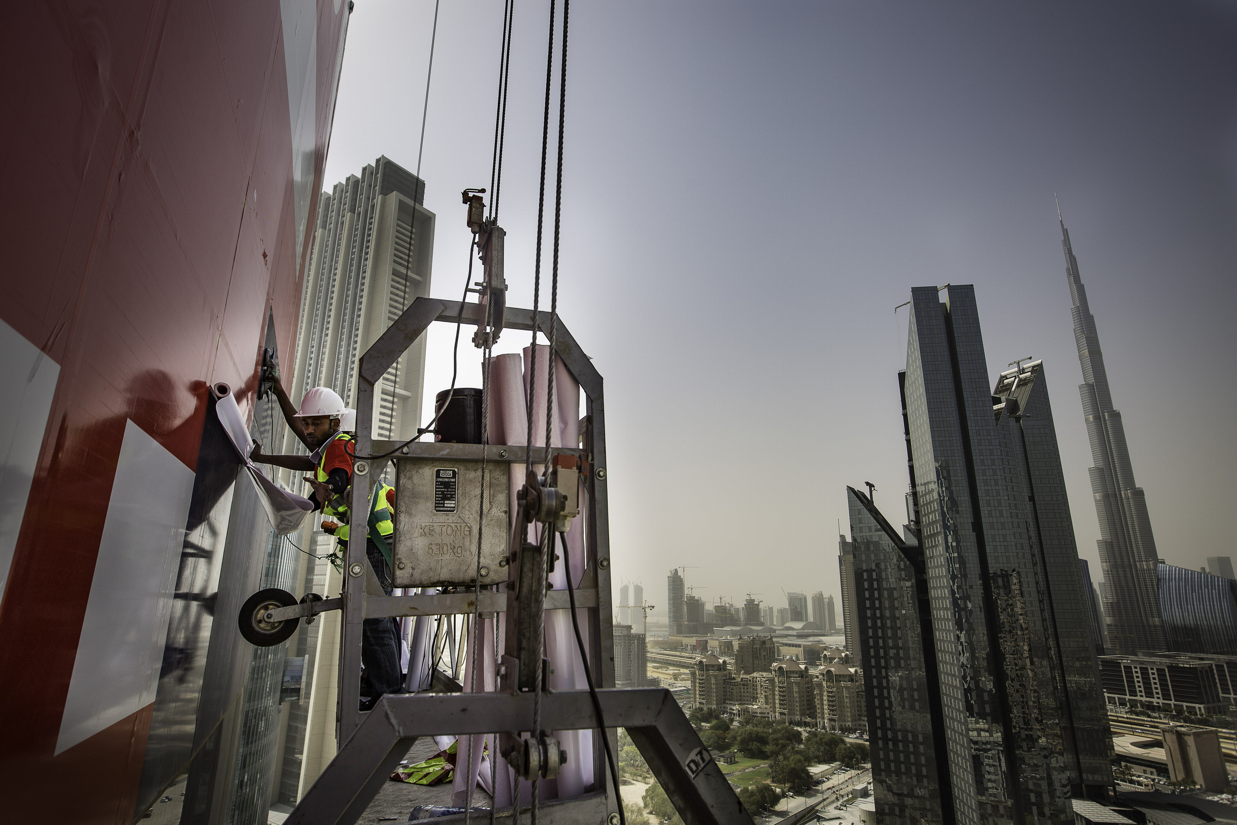 ENG advert applicators put up an advert on a building in Dubai.jpg