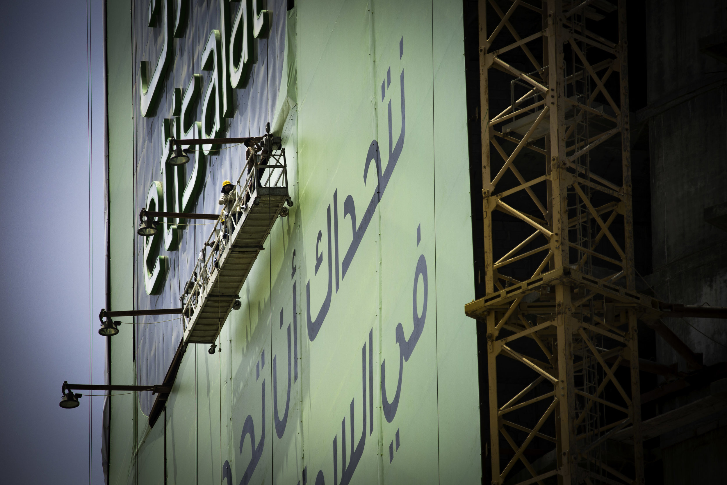 Workers put up an advert on a Dubai high-rise.jpg