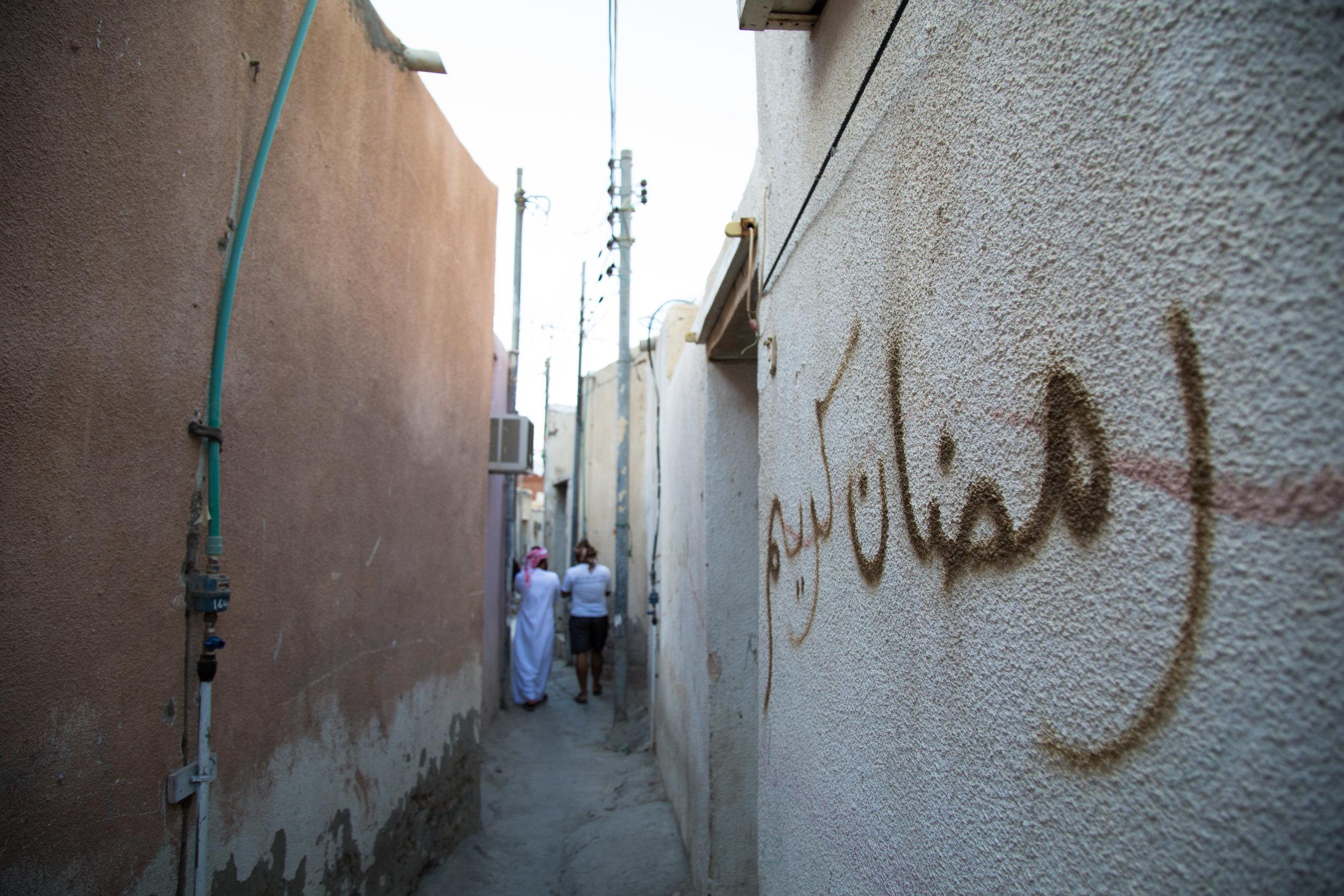 Ali Al Kumzari and Noufal Al Kumzari walk through Kumar's narrow alleys.jpg
