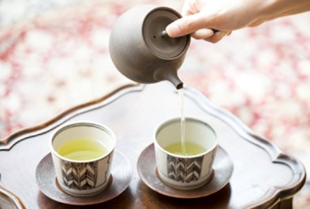 Green tea carefully brewed in a small teapot.