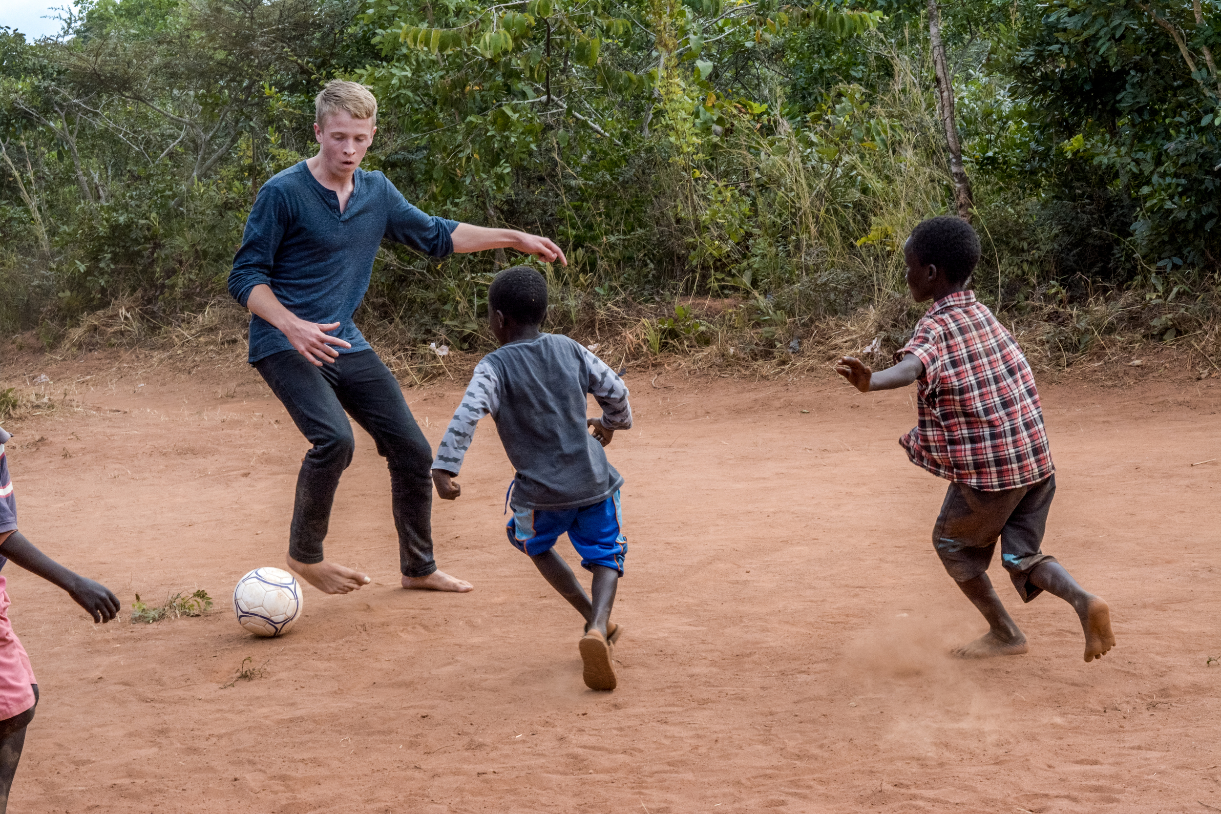 A photo of me playing soccer with the children in Viweme Village, Malawi.