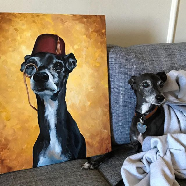 - Nuk, international dog of mystery, posing with his portrait.