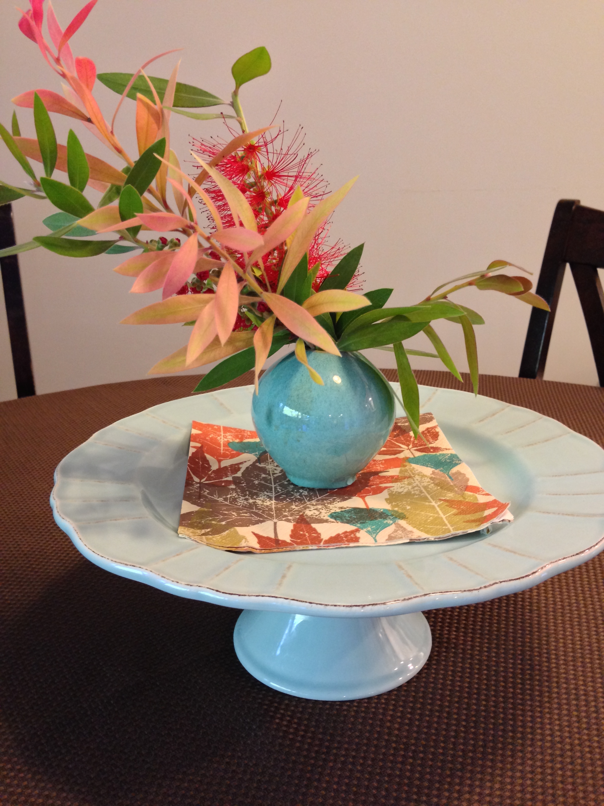 fall themed flower arrangement on cake stand