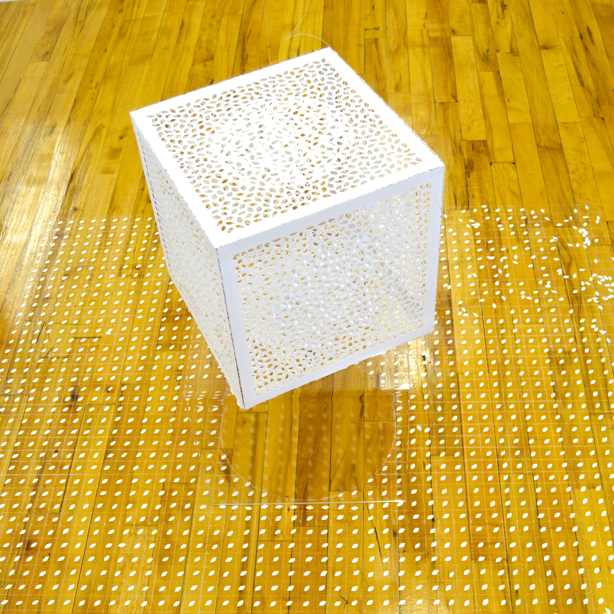 This 'floating' cube interplays with the cut-out pieces carefully placed below.