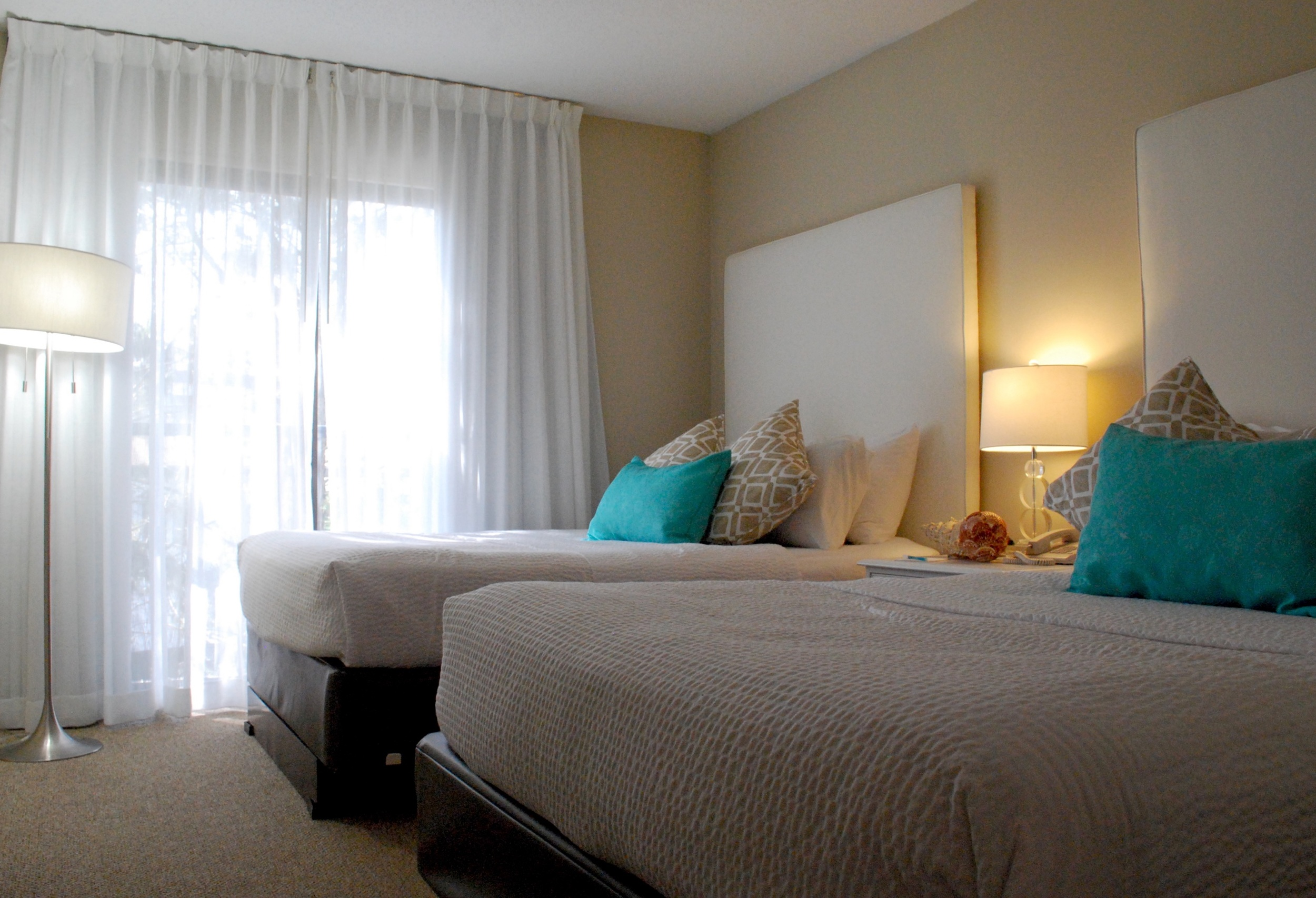 Double Suite: Two double beds, two televisions, DVD players, sleeper sofa, & wet-bar sink area.