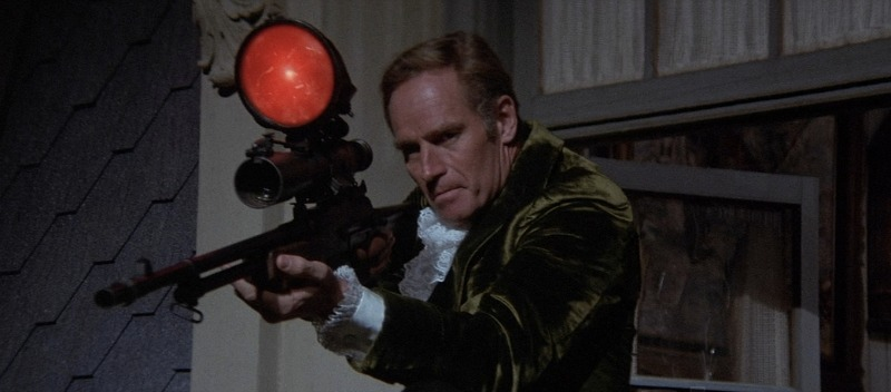 Charlton Heston, pictured here with the smallest gun he owned (Image Warner Bros.)