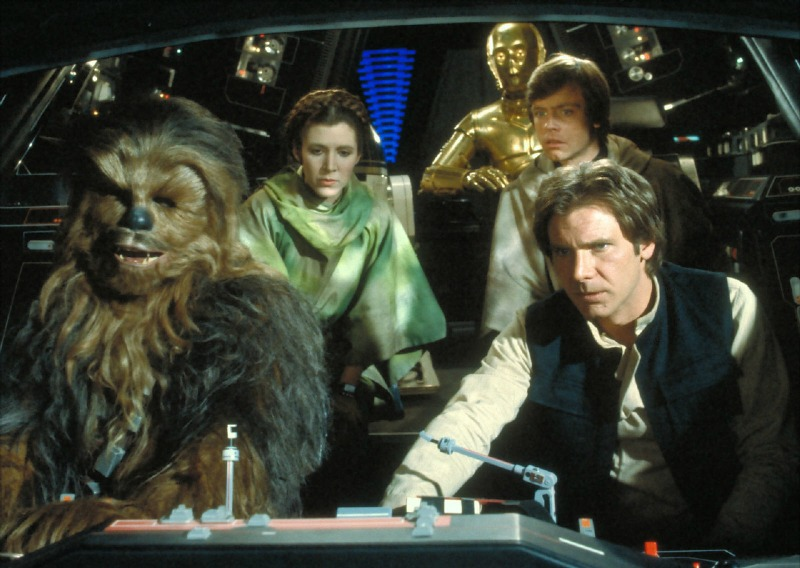 Peter Mayhew, Carrie Fisher, Anthony Daniels, Mark Hamill, and Harrison Ford in Return of the Jedi (Image  © Lucasfilm/Disney).