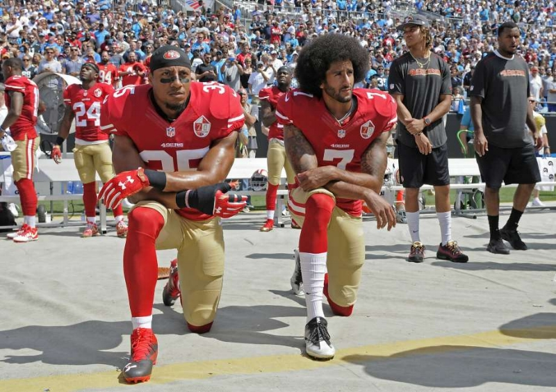 Eric Reid and Colin Kaepernick kneel before a game.