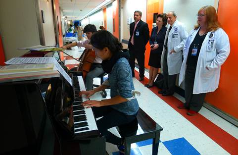 Performance in the hospital wing hallway with cellist, Mitchell Lyon, as part of the Gluck Community Service Fellowship