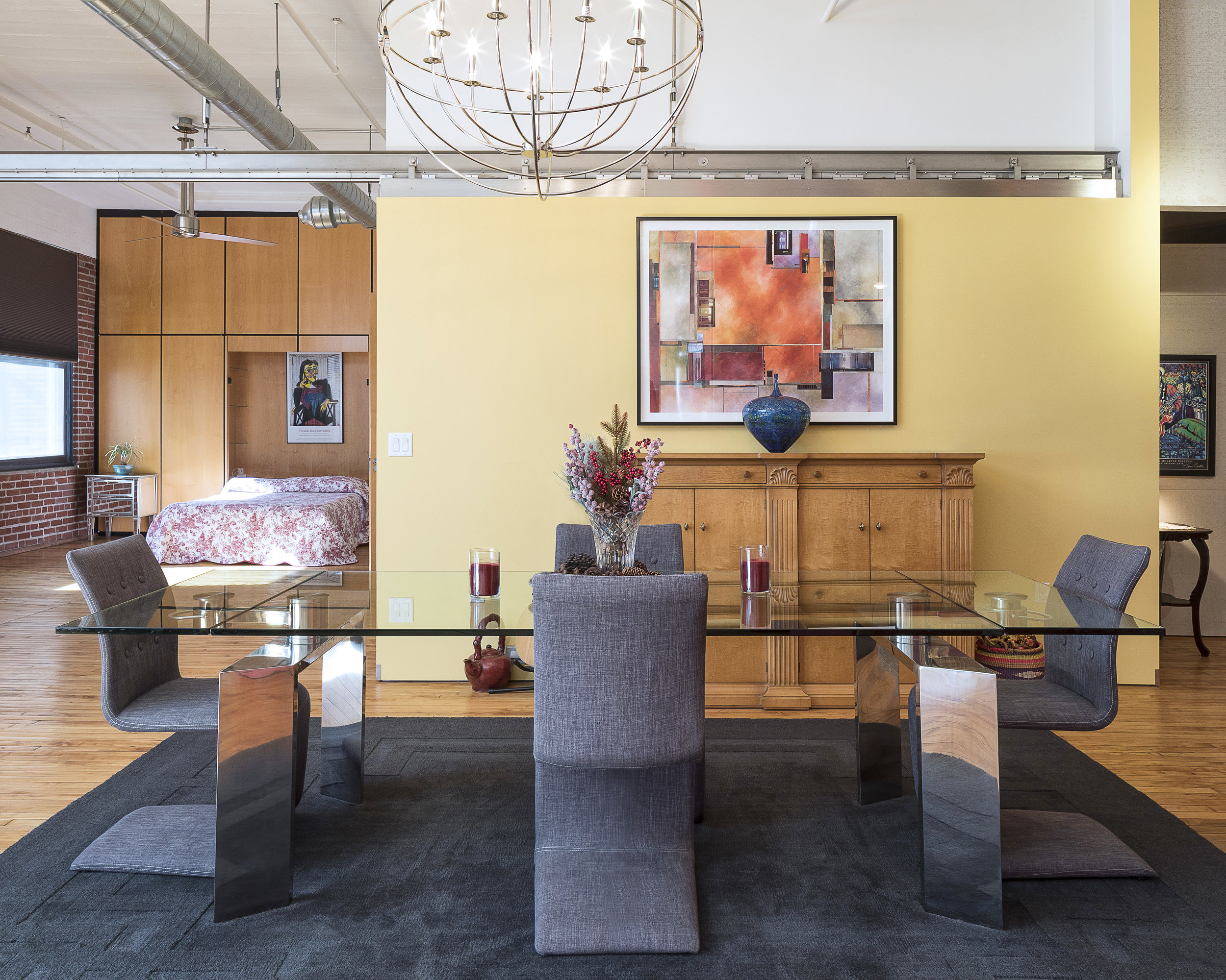 Downtown St. Louis, Missouri loft with yellow walls, a glass four chair table with dried flowers and deep red candles in the foreground, and a bedroom with a brick wall and tall yellow cabinets on the left. Photography by Jason Lusk of Missouri Home Tours, LLC.