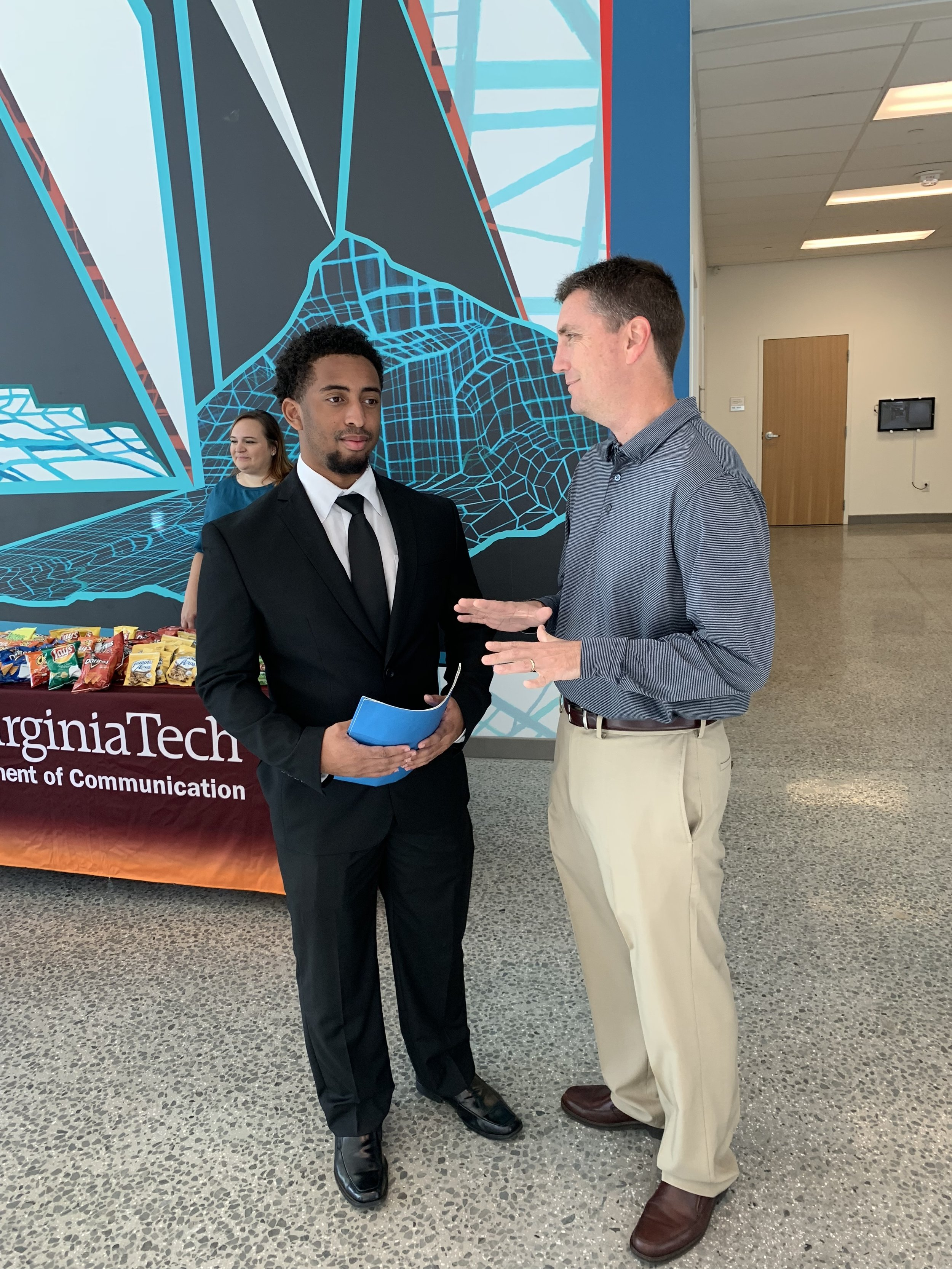 Sports Director Travis Wells of WDBJ-TV in Roanoke, Virginia visits with a Virginia Tech student at the Virginia Tech Communication Department 2018 Career Fair.