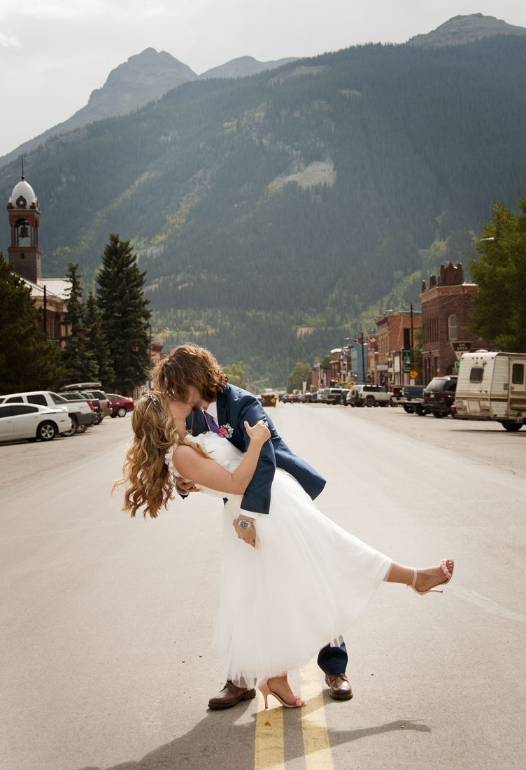 Groom dipping bride in road by photographers in durango co.jpg