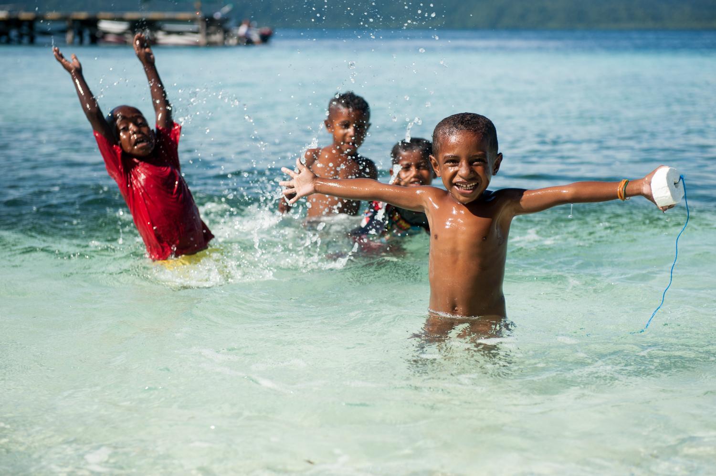 Arborek Island children having tons of fun in the water.