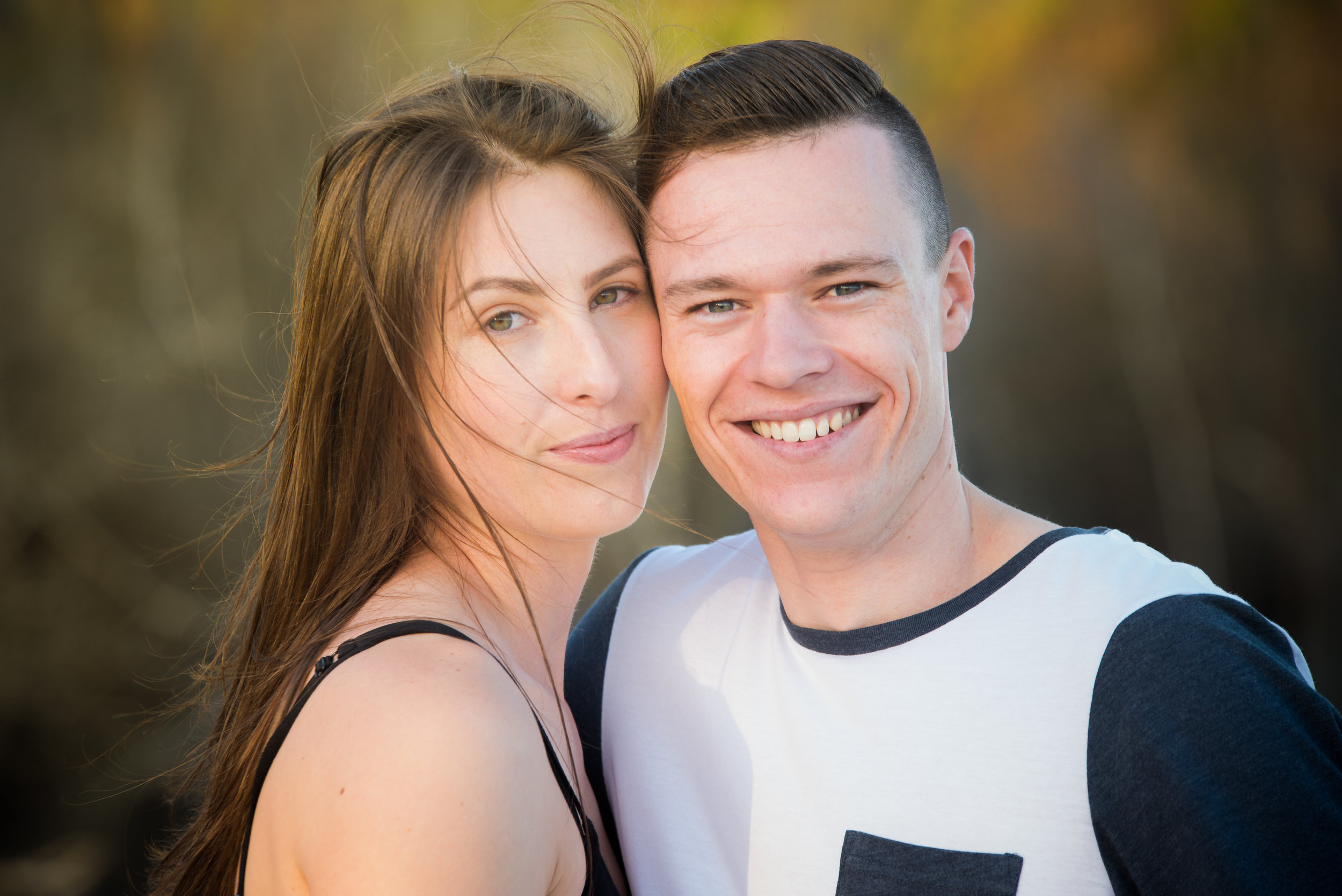 young engaged couple with blurred nature background