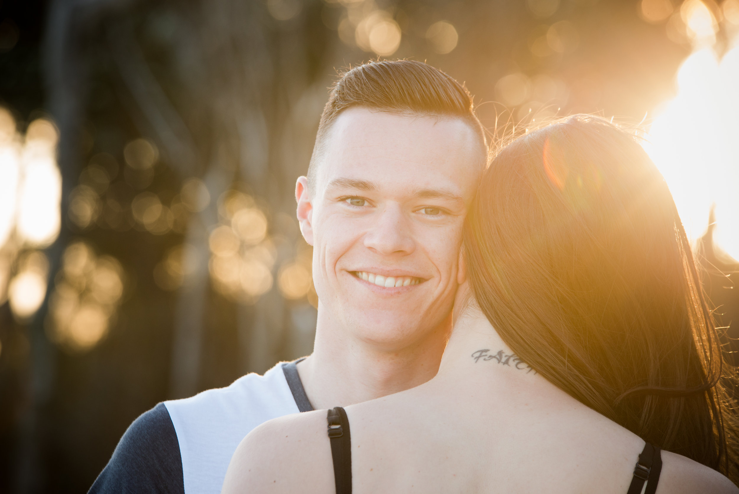 Young couple embrace with golden light filtering in behind